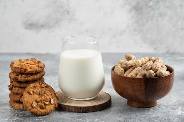 Bol de cacahuètes, verre de lait et biscuits aux cacahuètes biologiques sur table en marbre.