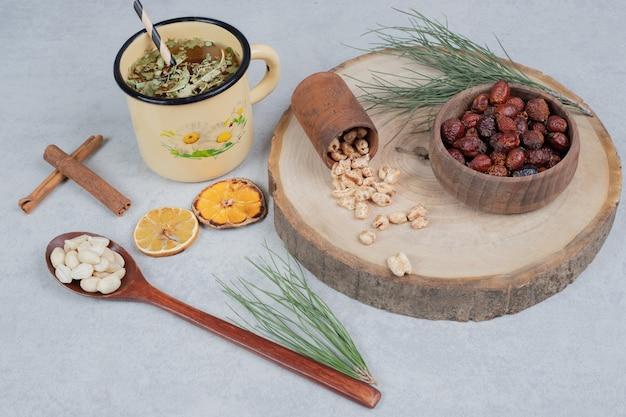 Bol de canneberges, collations et arachides sur fond gris. photo de haute qualité
