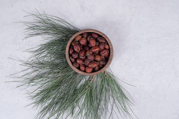 Bol de canneberges séchées et branche de pin sur table en marbre. photo de haute qualité