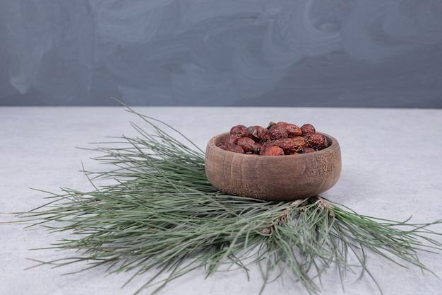 Bol de canneberges séchées et branche de pin sur table en marbre.