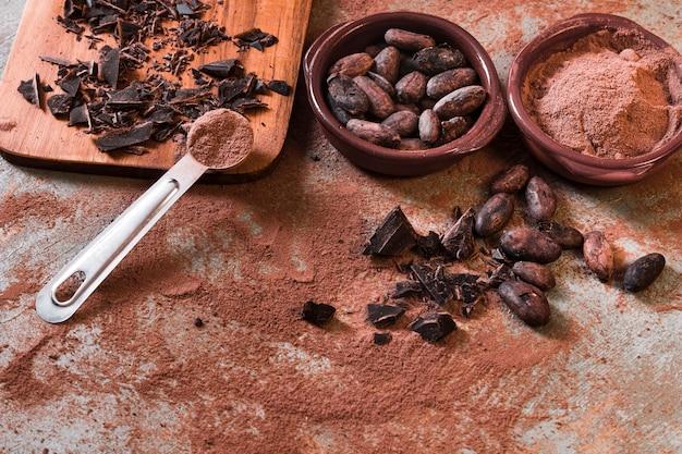 Bol cassé de fèves au chocolat et cacao sur toile de fond rustique