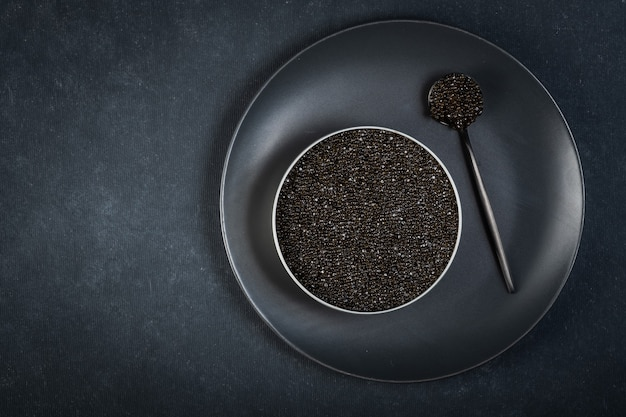 Bol de caviar noir de poisson d'esturgeon sur une surface bleu foncé.vue d'en haut