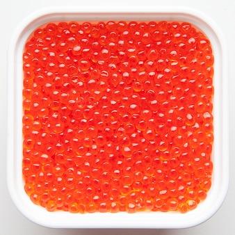 Bol de caviar rouge isolé sur un paysage blanc, vue du dessus