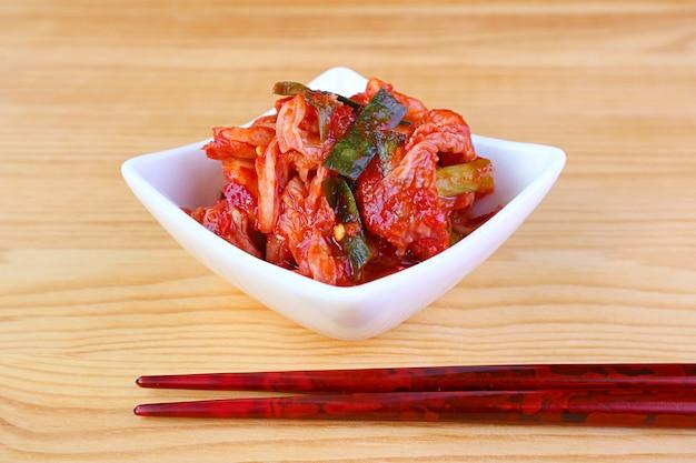 Bol de célèbre plat coréen kimchi avec une paire de baguettes sur table en bois