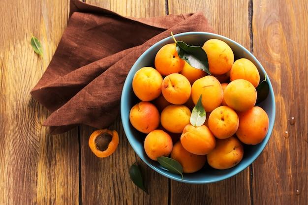 Bol en céramique d'abricots fraîchement récoltés sur une table en bois