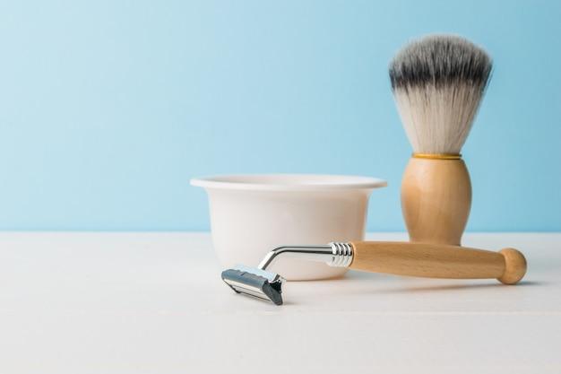 Un bol en céramique, un blaireau et un rasoir avec un manche en bois sur une table blanche. espace pour le texte.
