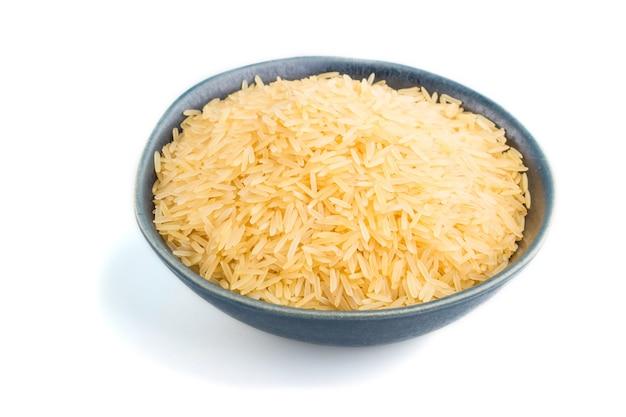 Bol en céramique bleu avec du riz doré cru isolé sur une surface blanche