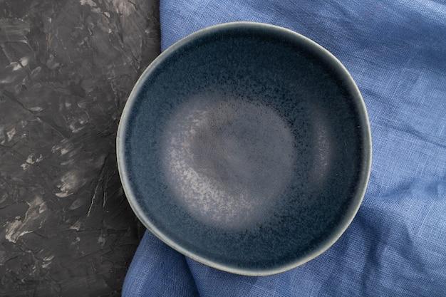 Bol en céramique bleu vide sur fond de béton noir et textile en lin bleu. vue de dessus, pose à plat.