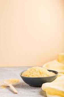Bol en céramique bleue avec riz doré brut et cuillère en bois sur fond gris et orange. vue latérale, espace copie.
