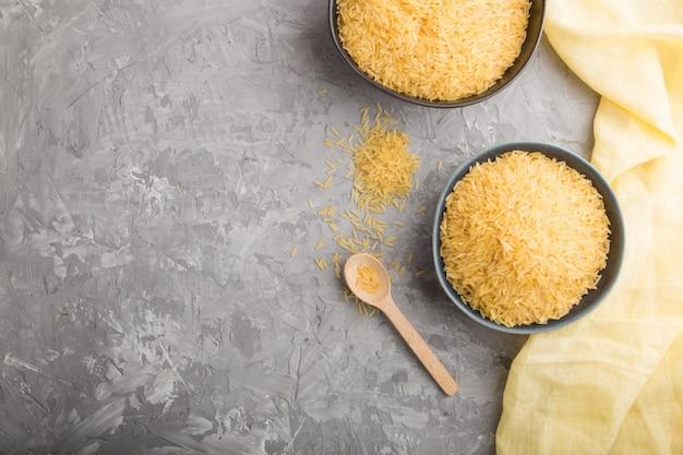 Bol en céramique bleue avec riz doré brut sur fond de béton gris
