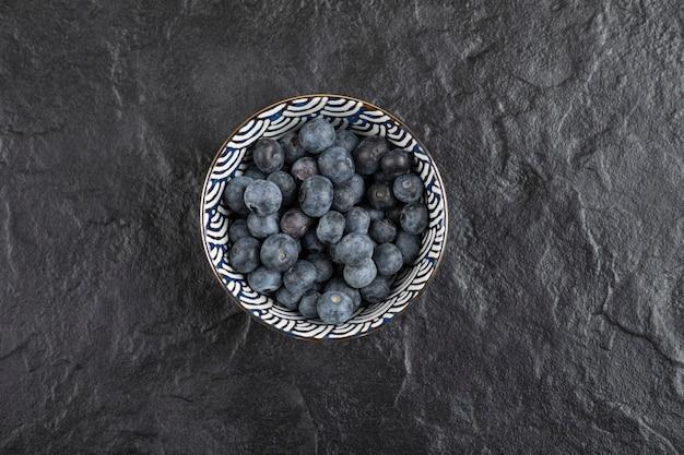 Bol en céramique de délicieux bleuets frais sur une surface noire