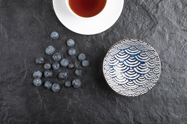 Bol en céramique de délicieux bleuets frais et tasse de thé sur une surface noire