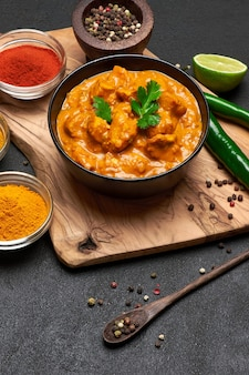 Bol en céramique noire de curry de poulet traditionnel et épices sur table sombre