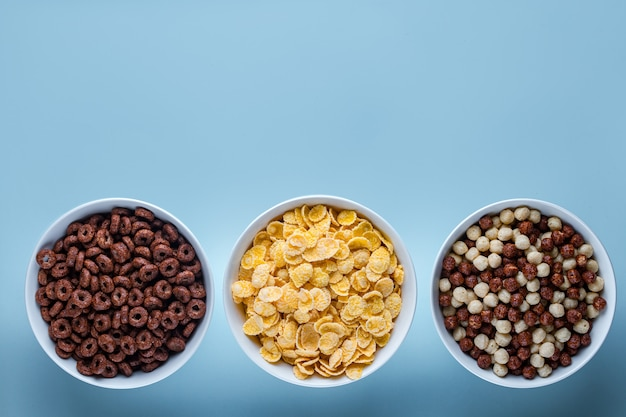 Bol à céréales avec des boules de chocolat, des anneaux et des flocons de maïs jaunes pour le petit déjeuner sec sur une surface bleue espace de copie, vue de dessus