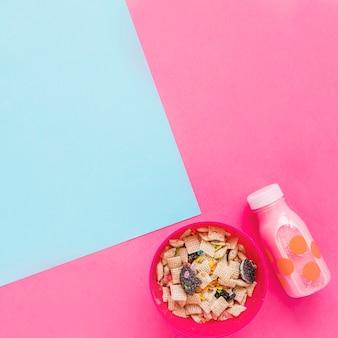 Bol avec céréales et bouteille de lait rose