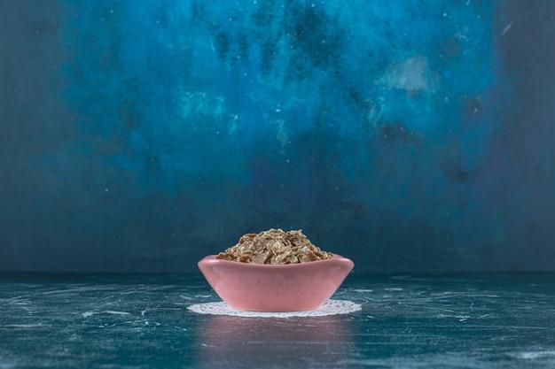 Un bol de céréales enrobées de sucre sur un sous-verre, sur la surface bleue