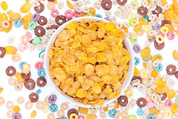 Bol de céréales flex de maïs et céréales éparpillées autour de la table sur blanc. vue de dessus.