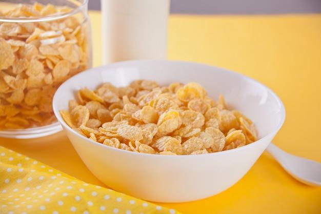 Un bol de céréales de flocons de maïs secs sur fond jaune