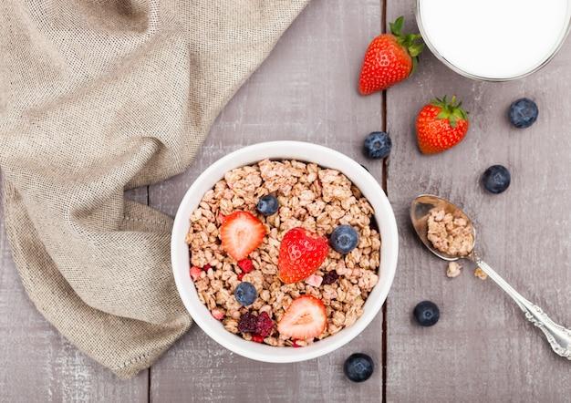 Bol de céréales granola sain avec des fraises et des bleuets et un verre de lait sur planche de bois