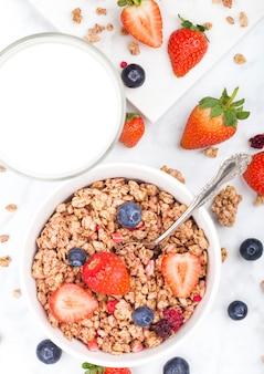 Bol de céréales granola sain avec des fraises et des bleuets et un verre de lait sur une planche en marbre