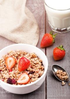 Bol de céréales granola sain avec des fraises et un verre de lait sur planche de bois