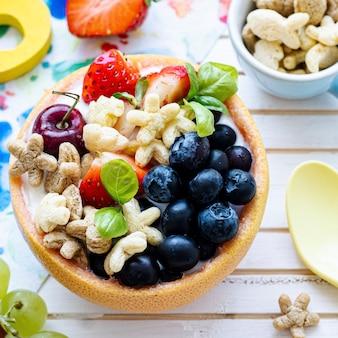 Bol de céréales pour enfants avec baies et yaourt