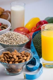 Bol de céréales, salade de fruits et nourriture sur une table blanche