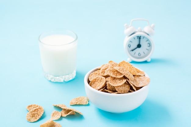 Un bol de céréales, un verre de lait et un réveil sur une table bleue. petit déjeuner programmé