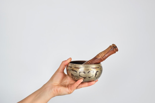 Bol chantant en cuivre et un bâton en bois dans une main féminine