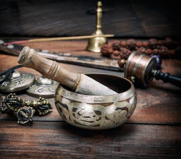 Bol chantant en cuivre et un bâton en bois sur une table marron