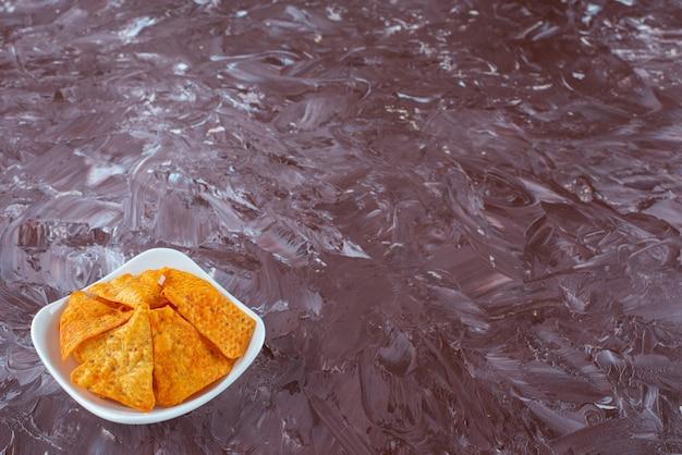 Un bol de chips épicées savoureuses, sur la table en marbre.
