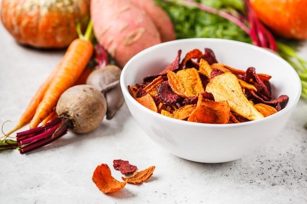 Bol de chips de légumes sains de betteraves, patates douces et carottes sur tableau blanc.