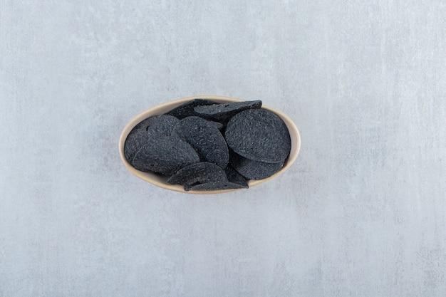Bol de chips noires croustillantes salées sur pierre.