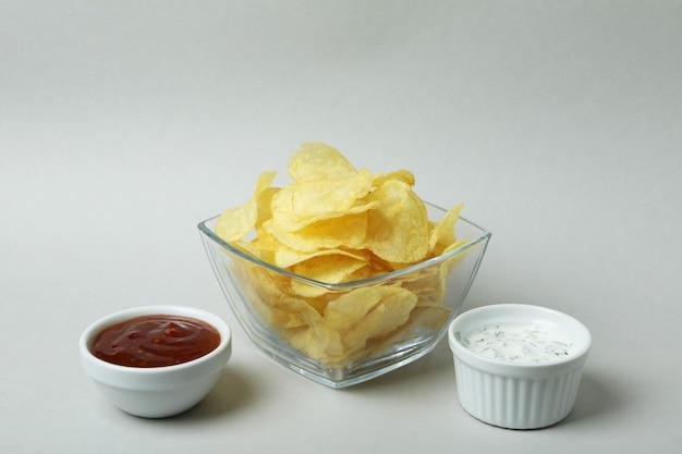 Bol de chips et sauces sur une surface gris clair