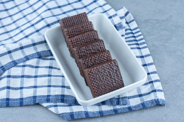 Un bol de chocolat enrobé d'une barre de gaufrettes croustillantes sur la serviette, sur la table en marbre.