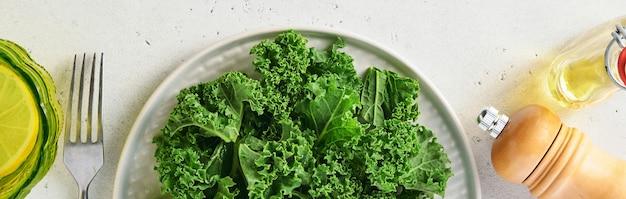Bol de chou frisé vert frais sur fond de pierre gris clair, vue de dessus. ingrédient pour faire une salade saine. concept d'alimentation propre, de désintoxication ou de régime. maquette. bannière.