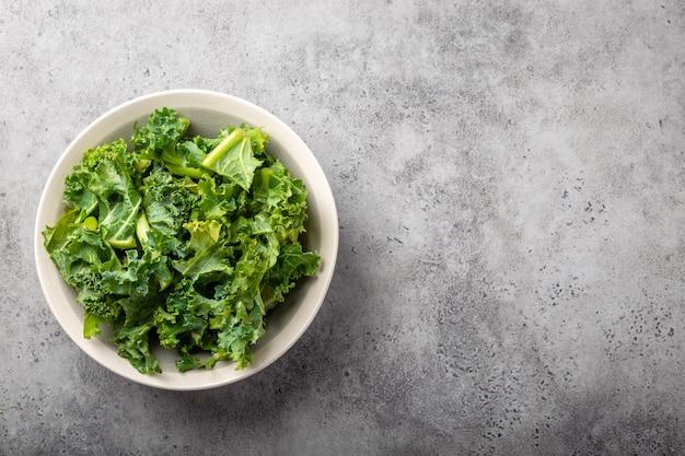 Bol de chou frisé vert frais sur fond de pierre rustique grise, vue de dessus, gros plan, espace de copie. ingrédient pour faire une salade saine. concept d'alimentation propre, de désintoxication ou de régime avec un espace pour le texte