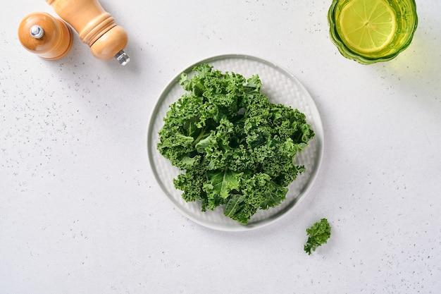 Bol de chou vert frais haché sur fond de pierre gris clair, vue du dessus. ingrédient pour faire une salade saine.