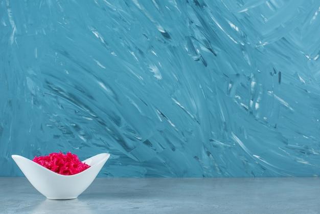 Un bol de choucroute fermentée rouge, sur la table bleue.