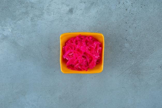 Un bol de choucroute rouge, sur la table bleue.