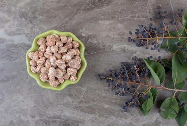 Un bol de confiserie avec du raisin et des feuilles, sur la surface en marbre