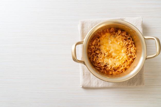 Bol coréen de nouilles instantanées épicées avec fromage mozzarella