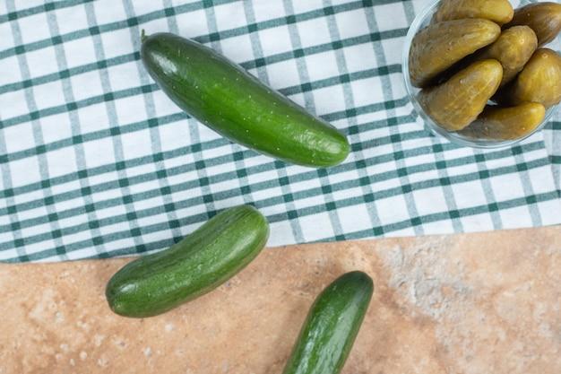 Bol de cornichons et concombres frais sur nappe.