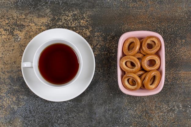 Bol de craquelins et tasse de thé sur marbre.