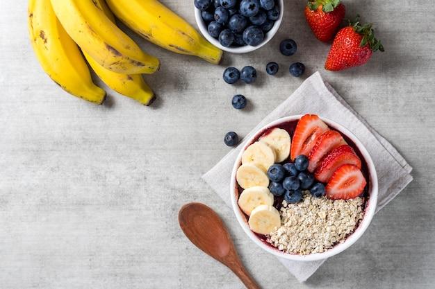Bol de crème glacée brésilienne congelée et aux baies d'açai avec des fraises, des bananes, des flocons de bleuets et d'avoine. avec des fruits sur fond en bois. vue de dessus du menu d'été. fermer