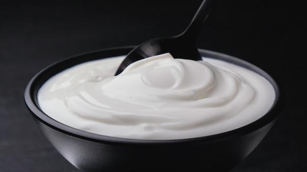 Bol de crème sure sur noir, yogourt grec avec cuillère