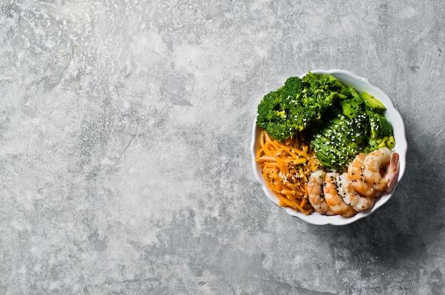 Bol avec crevettes, avocat, carotte, brocoli et riz. plat végétarien équilibré.