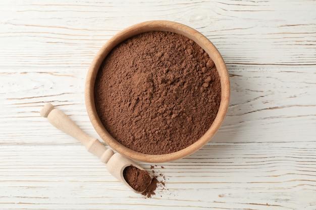 Bol et cuillère en bois avec poudre de cacao sur bois blanc, vue du dessus