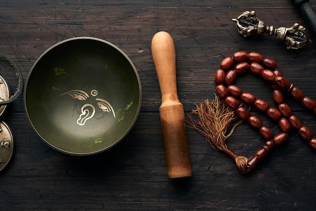Bol en cuivre chantant tibétain avec un battant en bois sur un woo brun