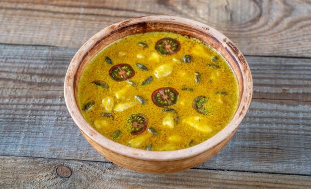 Bol de curry aux champignons jaunes sur la table en bois